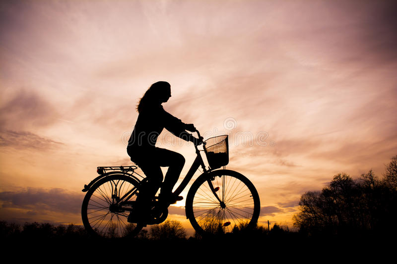 Silhouette de la fille sur la bicyclette photographie stock libre de droits