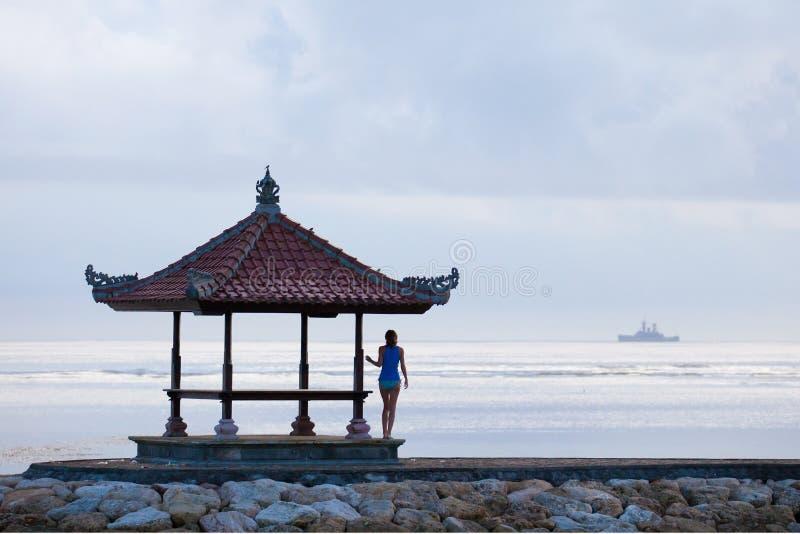 Silhouette de la fille sur le pilier et le bateau à l'horizon photo stock