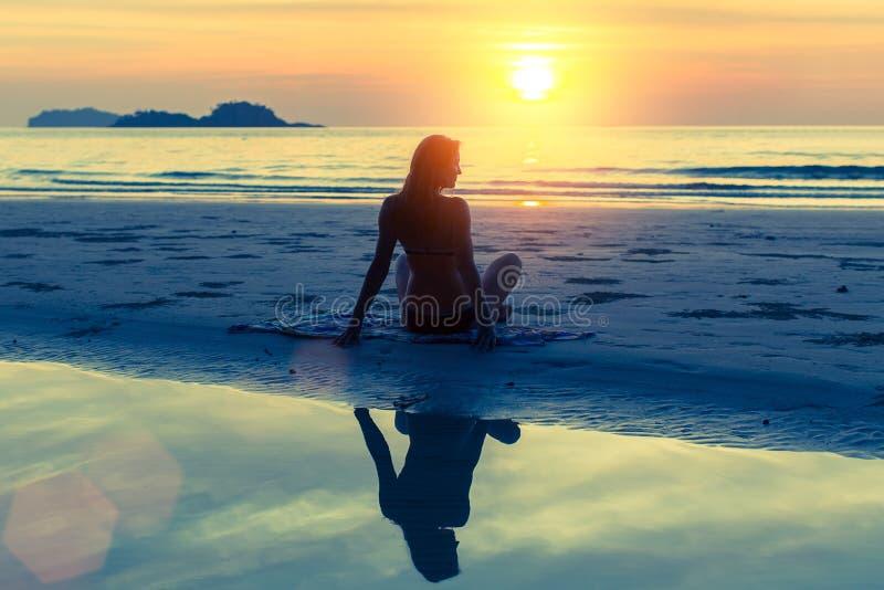 Silhouette de la jeune belle fille s'asseyant sur la plage images stock