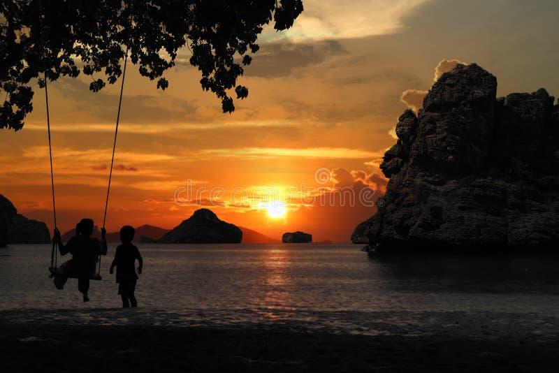 Silhouette de la mère et du fils s'asseyant sur le berceau ou hamac sur la plage avec le coucher du soleil rouge de ciel photos libres de droits