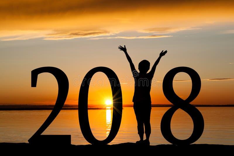 Silhouette de la nouvelle année 2018 de femme au coucher du soleil d'or photographie stock libre de droits