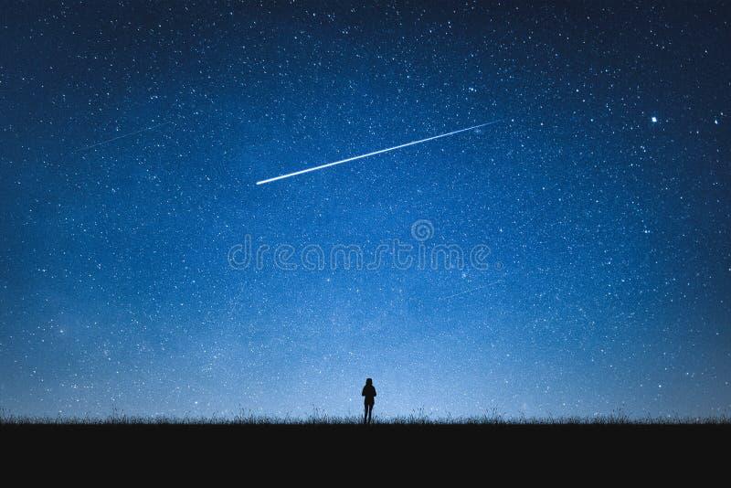 Silhouette de la position de fille sur la montagne et le ciel nocturne avec l'étoile filante seul concept photos stock