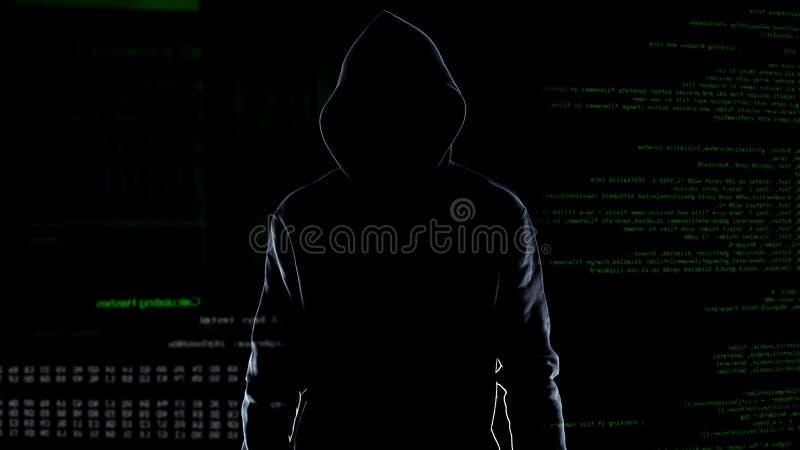 Silhouette de la position masculine courageuse de pirate informatique sur le fond animé de code informatique images stock