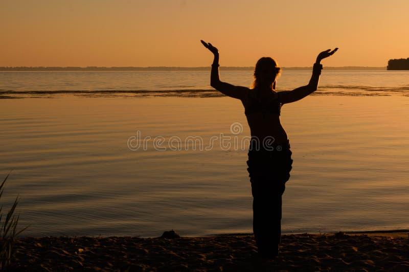 Silhouette de la tradition de danse de femme oriental trible près de grande côte de rivière image stock