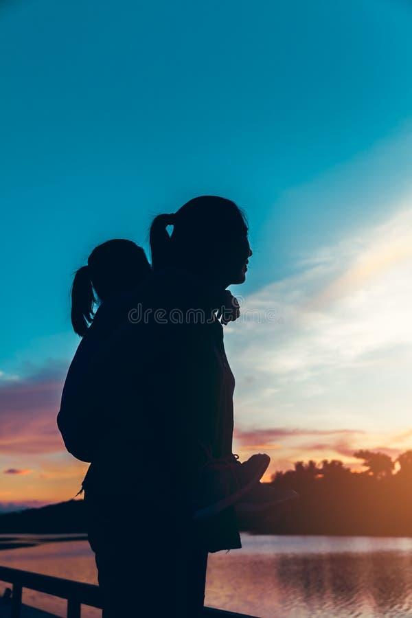 Silhouette de mère et sa fille appréciant la vue à la rive photos stock