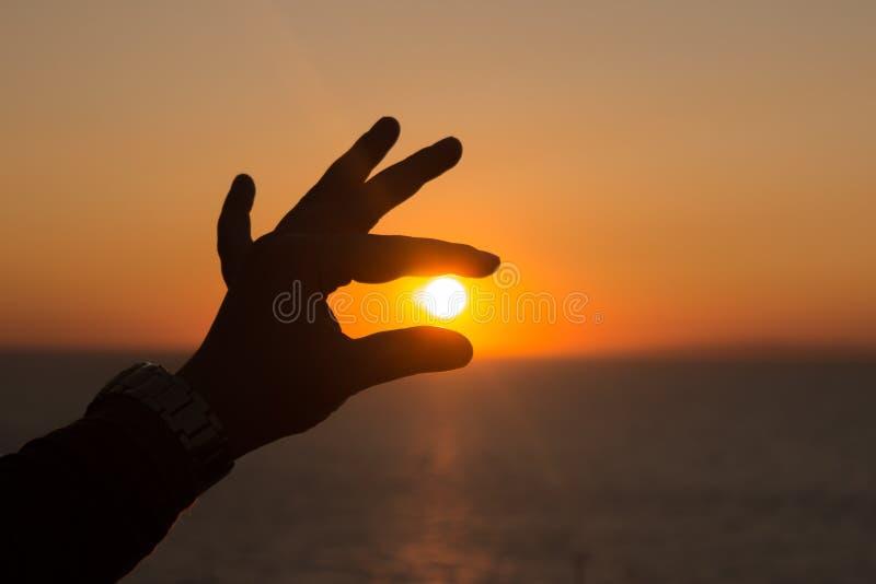 Silhouette de main au coucher du soleil photos stock