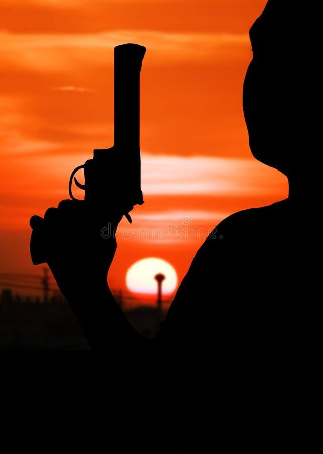 silhouette de main de l'homme tenant des revolvers d'arme à feu image libre de droits