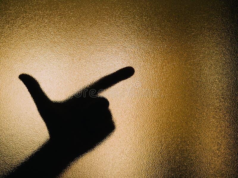 Silhouette de main faisant un revolver sur un verre image libre de droits