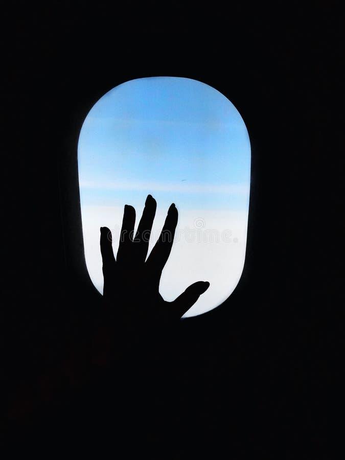Silhouette de main de femme à la fenêtre d'avions d'avion Voyage avec le concept de transport aérien images libres de droits