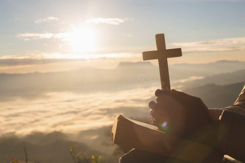 Silhouette de main de femme tenant l'ascenseur saint de la croix chrétienne avec le fond clair de coucher du soleil images stock