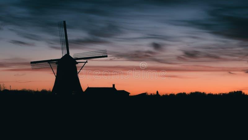 Silhouette de moulin à vent néerlandais traditionnel au coucher du soleil au coucher du soleil photos libres de droits