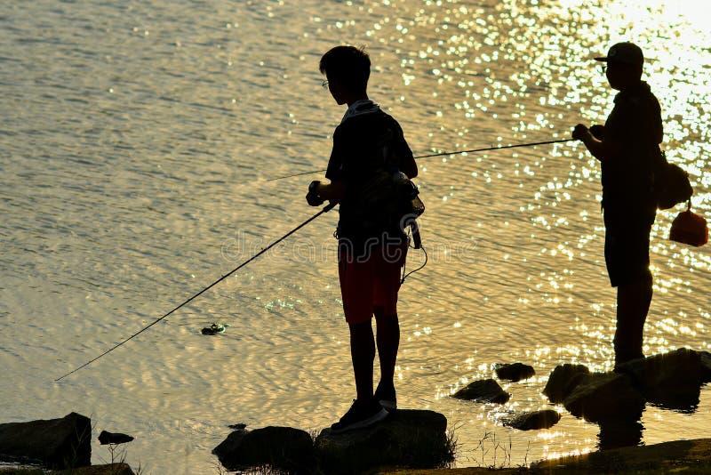 Silhouette de pêche de coucher du soleil image libre de droits