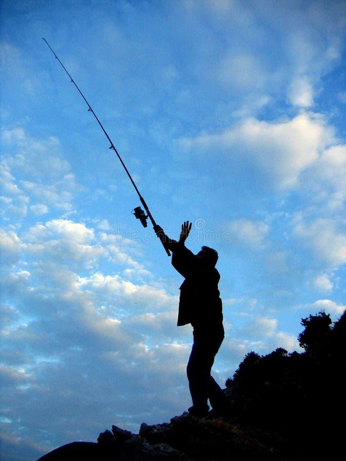 Silhouette de pêcheur photos stock