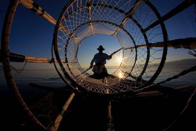 Silhouette de pêcheur d'intha contre le ciel de coucher du soleil image stock