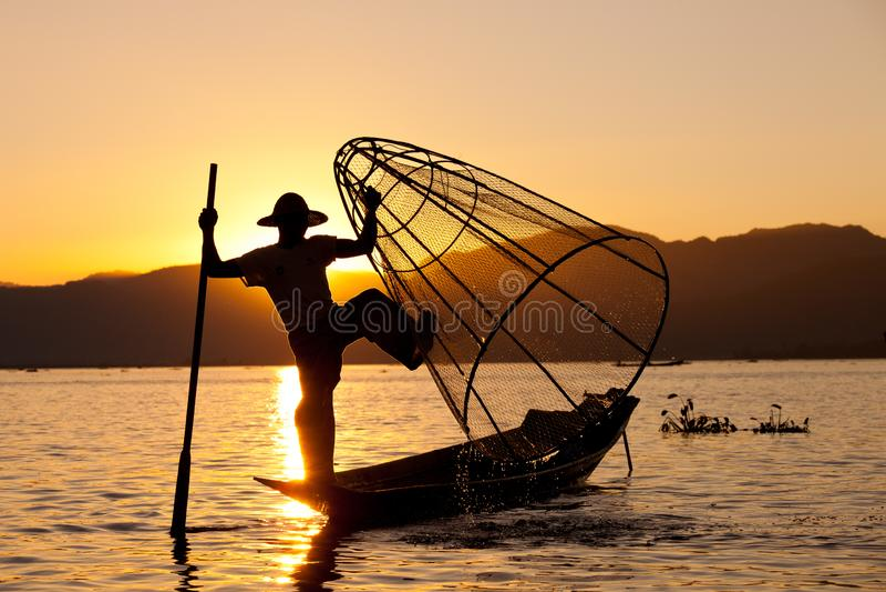 Silhouette de pêcheur de Myanmar sur le bateau en bois au coucher du soleil Pêcheur birman sur les poissons de capture de bateau  photo stock