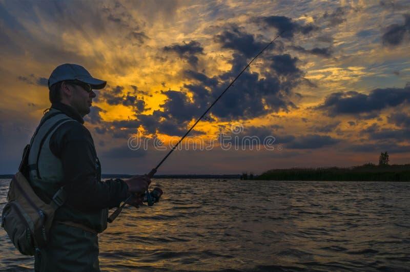 Silhouette de p?cheur Homme dans l'eau avec la canne à pêche sur le fond nuageux de coucher du soleil images stock