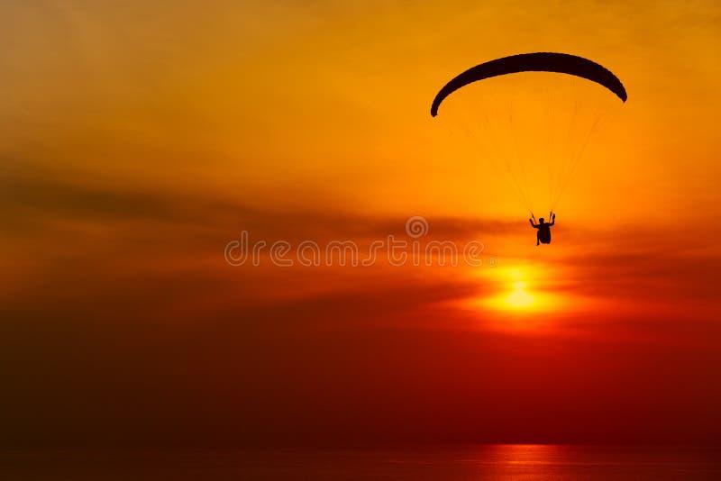 Silhouette de parapentiste dans la perspective du ciel de coucher du soleil images stock