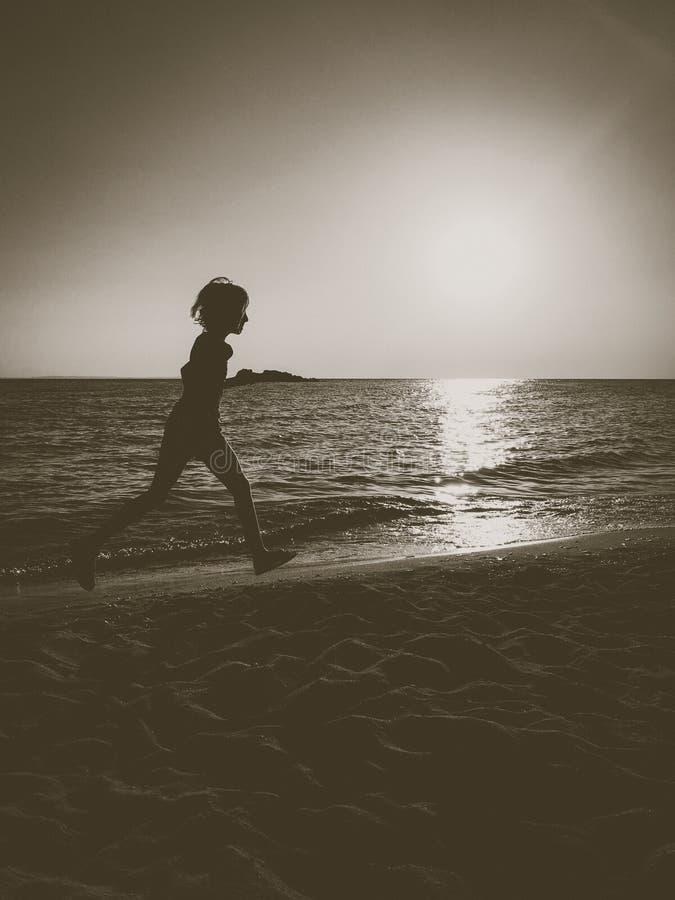 Silhouette de petite fille fonctionnant sur la plage dans le coucher du soleil image stock