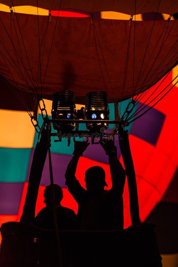 Silhouette de pilote dans le panier chaud de ballon à air utilisant le brûleur avec la belle enveloppe colorée à l'arrière-plan photos libres de droits