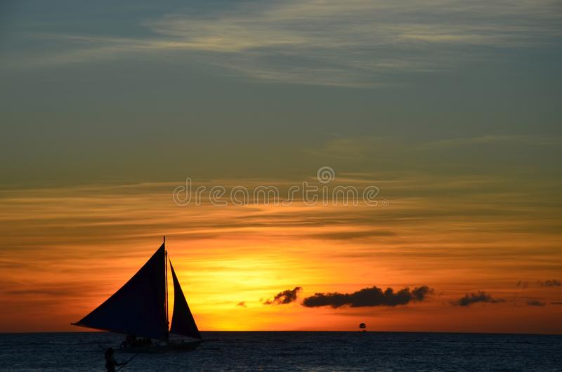 Silhouette de planche à voile contre le coucher du soleil image stock