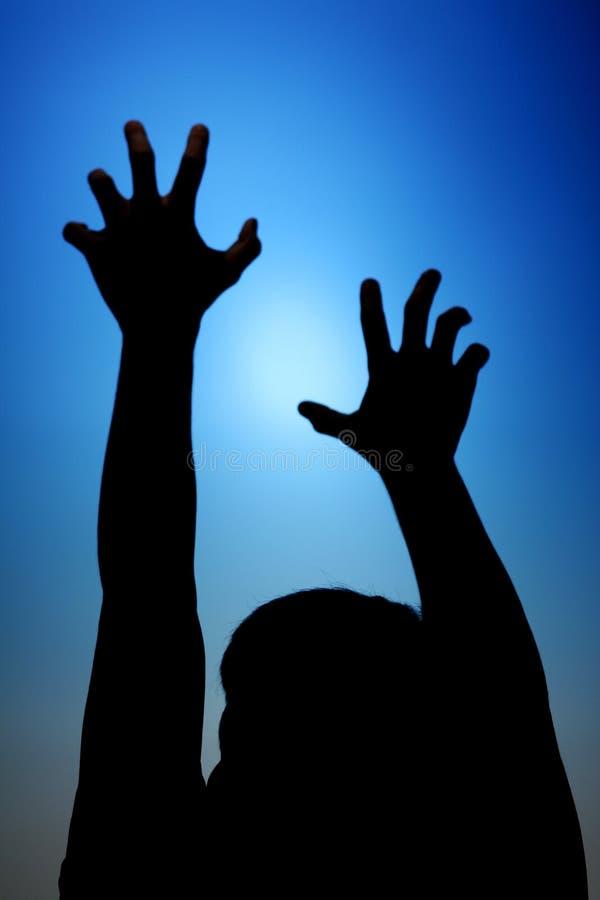 Silhouette de portée de l'homme vers le ciel photo stock
