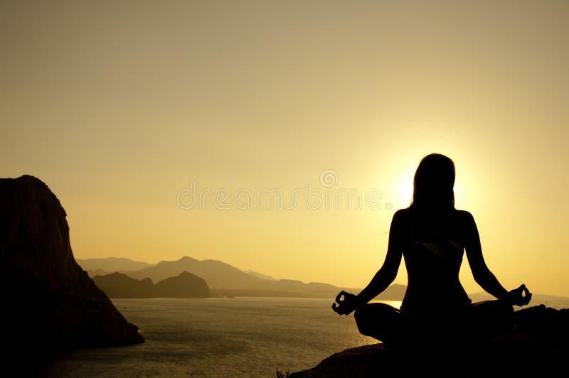 Silhouette de position de lotus de yoga sur le bord de la mer photo libre de droits