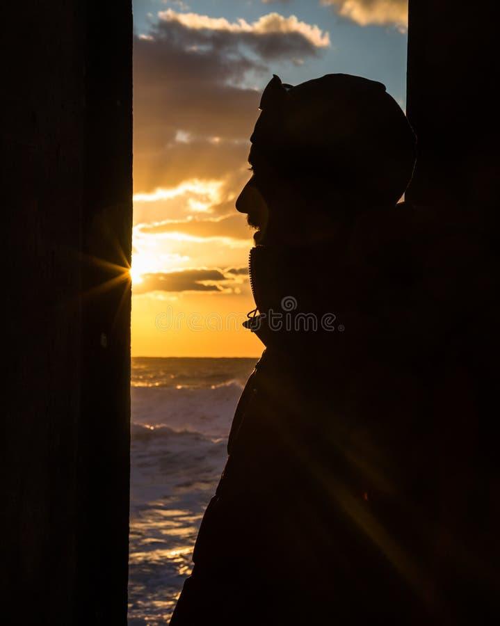 Silhouette de profil du visage du jeune homme avec le coucher de soleil au-dessus de l'océan image libre de droits