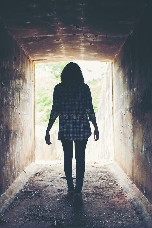 Silhouette de promenade de femme de hippie dans le tunnel Lumière à l'extrémité de la tonne image stock