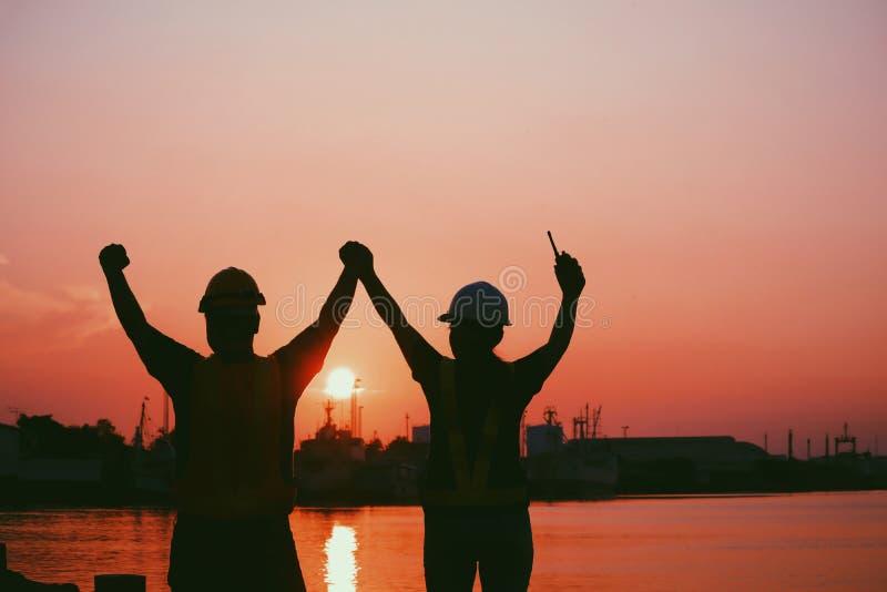 Silhouette de quelques conjoints des ingénieurs tenant des mains ainsi que gai au pilier travailleur et ingénieur images stock