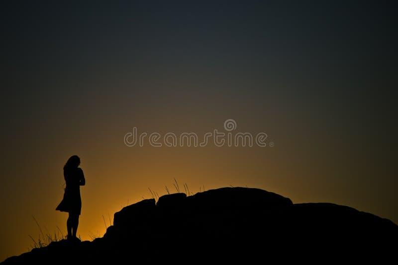 Silhouette de roche et de femme photographie stock libre de droits