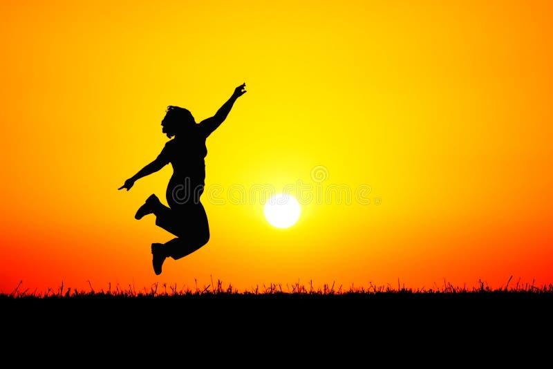 Silhouette de sauter de personne de la joie au coucher du soleil  image libre de droits