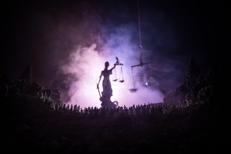 Silhouette de statue géante brouillée de justice de dame avec l'épée et d'échelle se tenant derrière la foule la nuit avec le fon images libres de droits