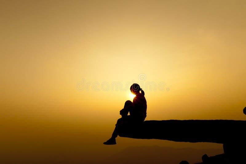 Silhouette de succès de femme sur la montagne supérieure au coucher du soleil, sélective image libre de droits