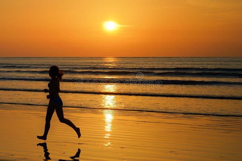 Silhouette de taqueur de femme fonctionnant sur la plage de coucher du soleil avec la réflexion, la forme physique et le sport photos libres de droits