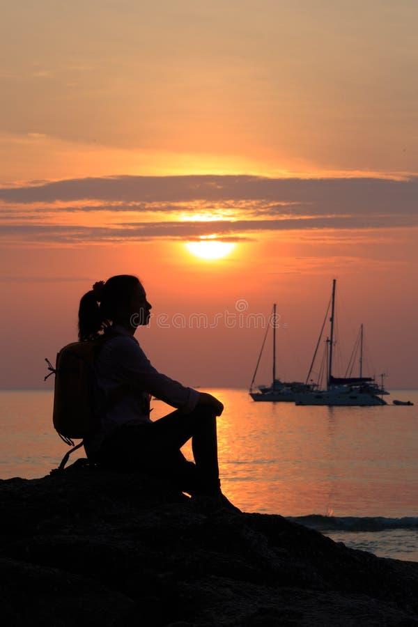 Silhouette de temps de coucher du soleil de femmes sur la plage images libres de droits