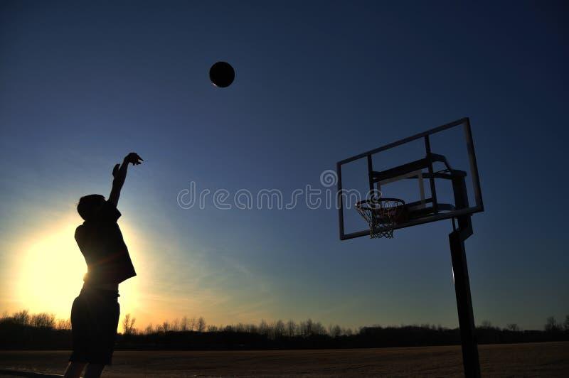 silhouette de tir de garçon de basket-ball de l'adolescence photo stock