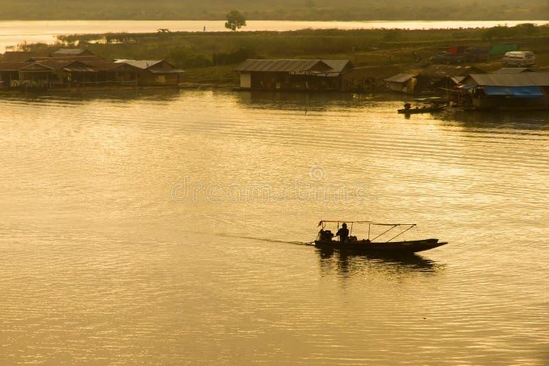 Silhouette de tour de bateau d'homme de canotage en rivière au coucher du soleil à SA image stock