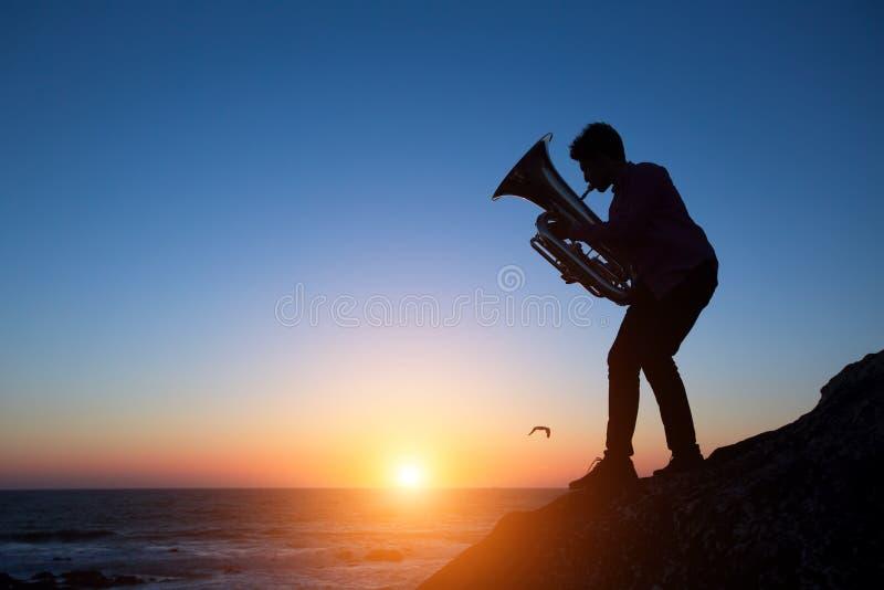Silhouette de tuba de jeu de musicien sur le bord de mer au coucher du soleil étonnant Art photographie stock libre de droits