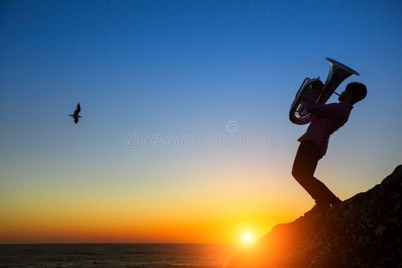 Silhouette de tuba de jeu de musicien sur le bord de mer au coucher du soleil roman image libre de droits