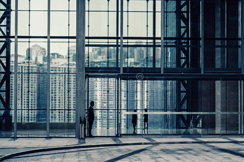 Silhouette de un hombre parado frente a una pared cortina en un edificio con ventanas foto de archivo
