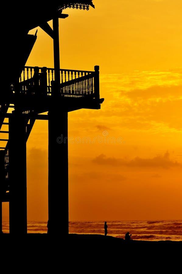 Silhouette de véranda à la plage pendant le lever de soleil avec des personnes à photos stock