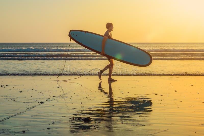 Silhouette de vacances d'un surfer portant sa maison de panneau de ressac au coucher du soleil avec l'espace de copie photo stock