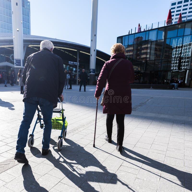 Silhouette de vieil homme derrière le marcheur et la femme avec le bâton de marche photographie stock libre de droits