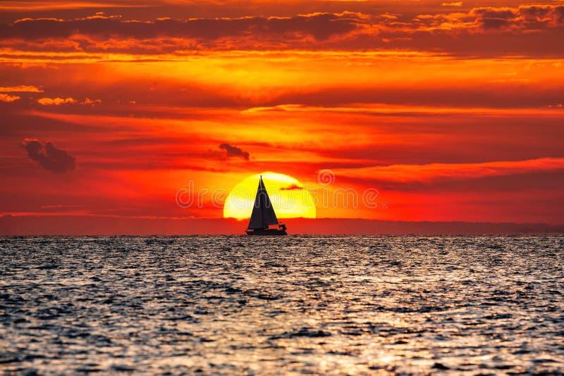Silhouette de voilier devant un grand coucher de soleil photo stock