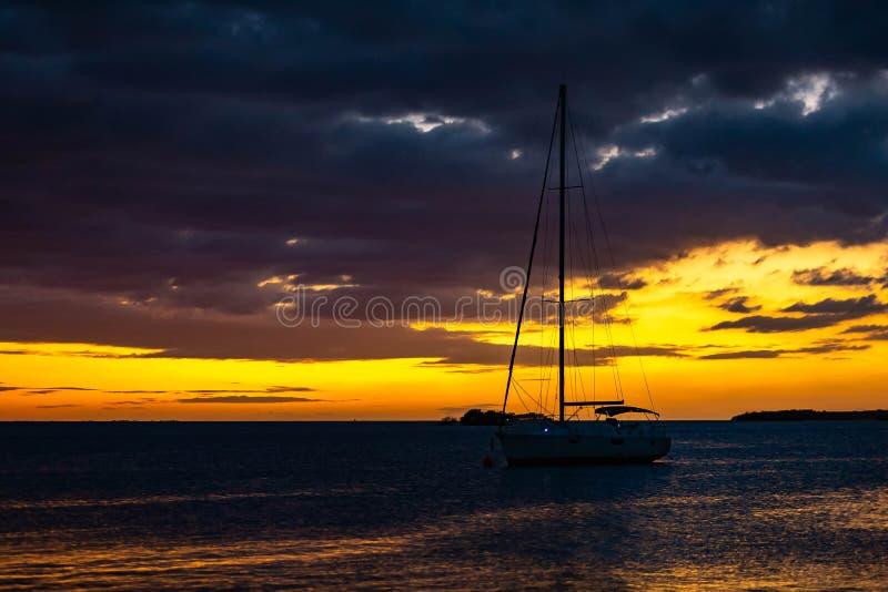 Silhouette de yacht au coucher du soleil au bord de mer photographie stock libre de droits