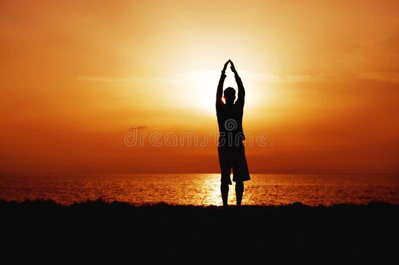 Silhouette de yoga de pratique de jeune homme Coucher du soleil sur la position arrière de courbure de littoral, Anuvittasana photos stock