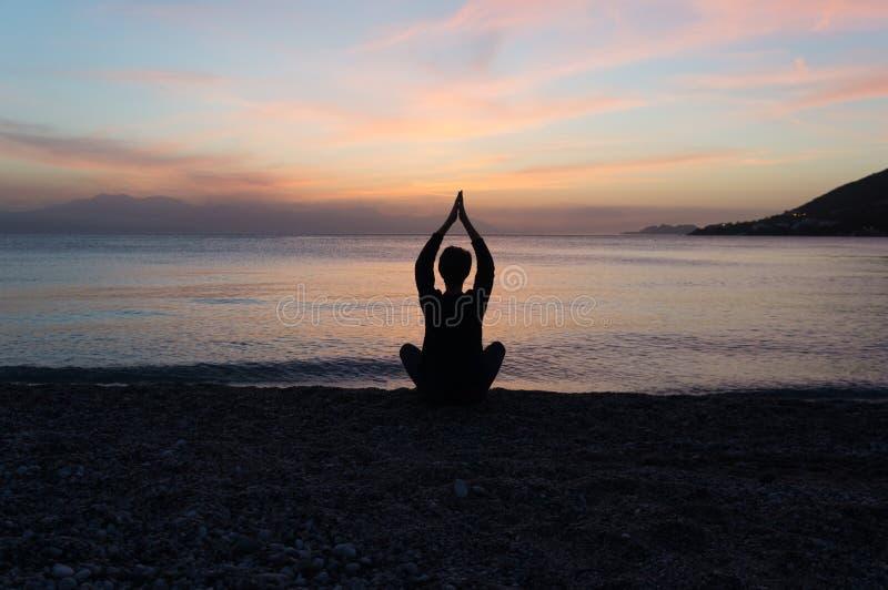 Silhouette de yoga sur la plage au coucher du soleil photo libre de droits