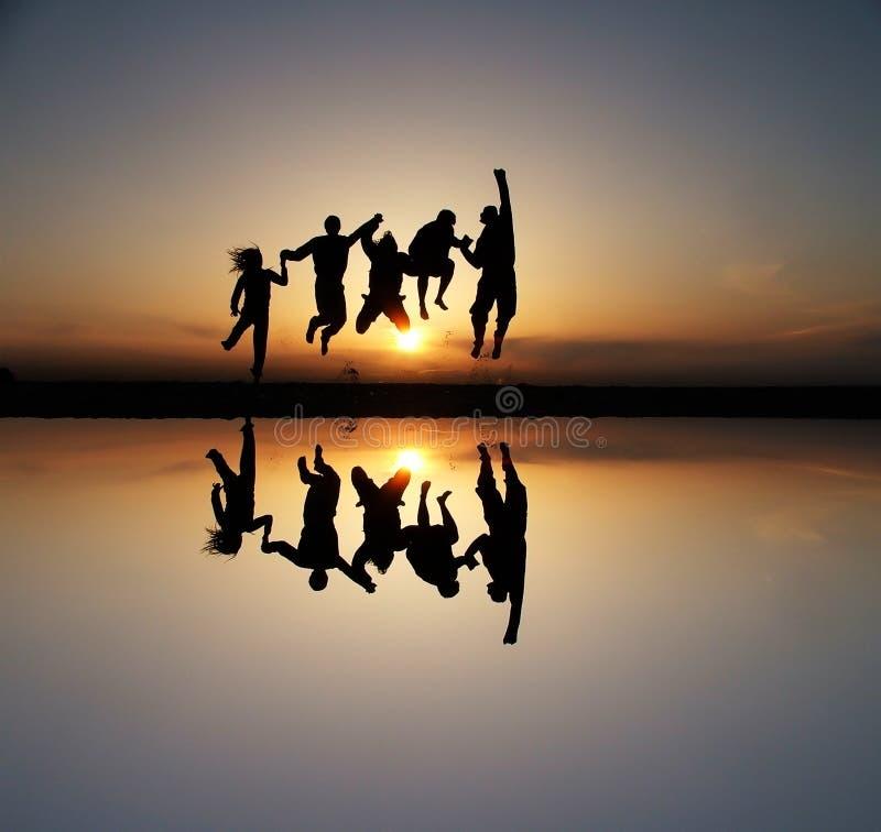 Silhouette des amis au coucher du soleil images libres de droits