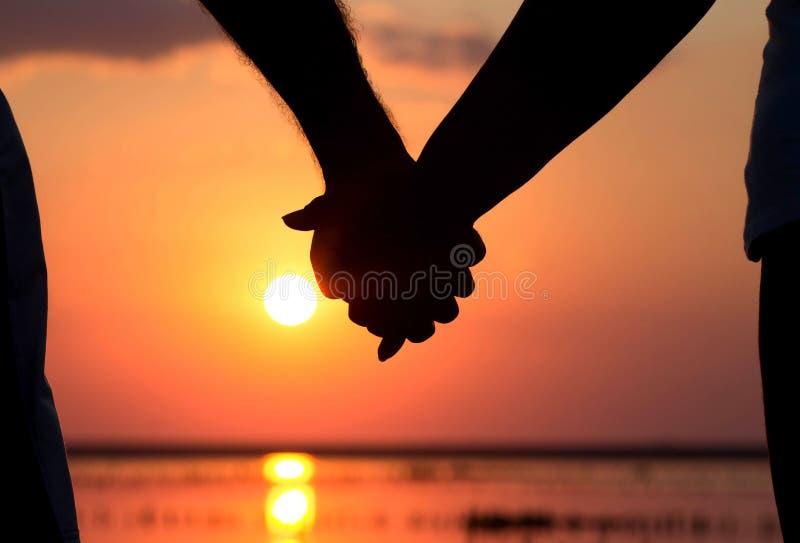 Silhouette des couples au coucher du soleil tenant des mains photos libres de droits