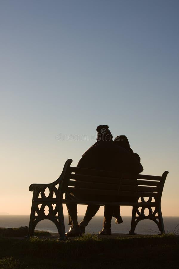 Silhouette des couples sur le banc photographie stock libre de droits